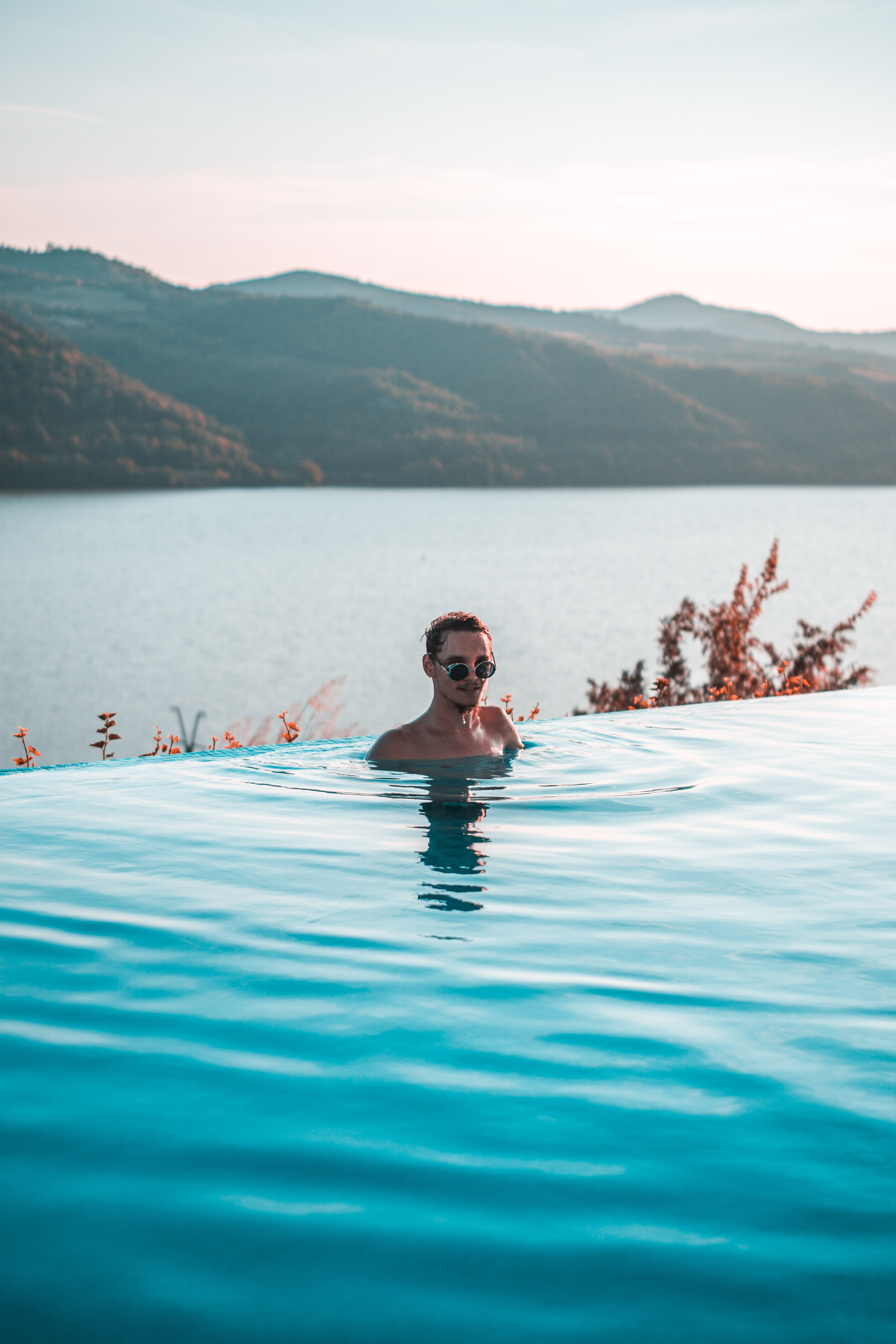 man wearing black sunglasses swimming on infinity pool near body of water at daytime