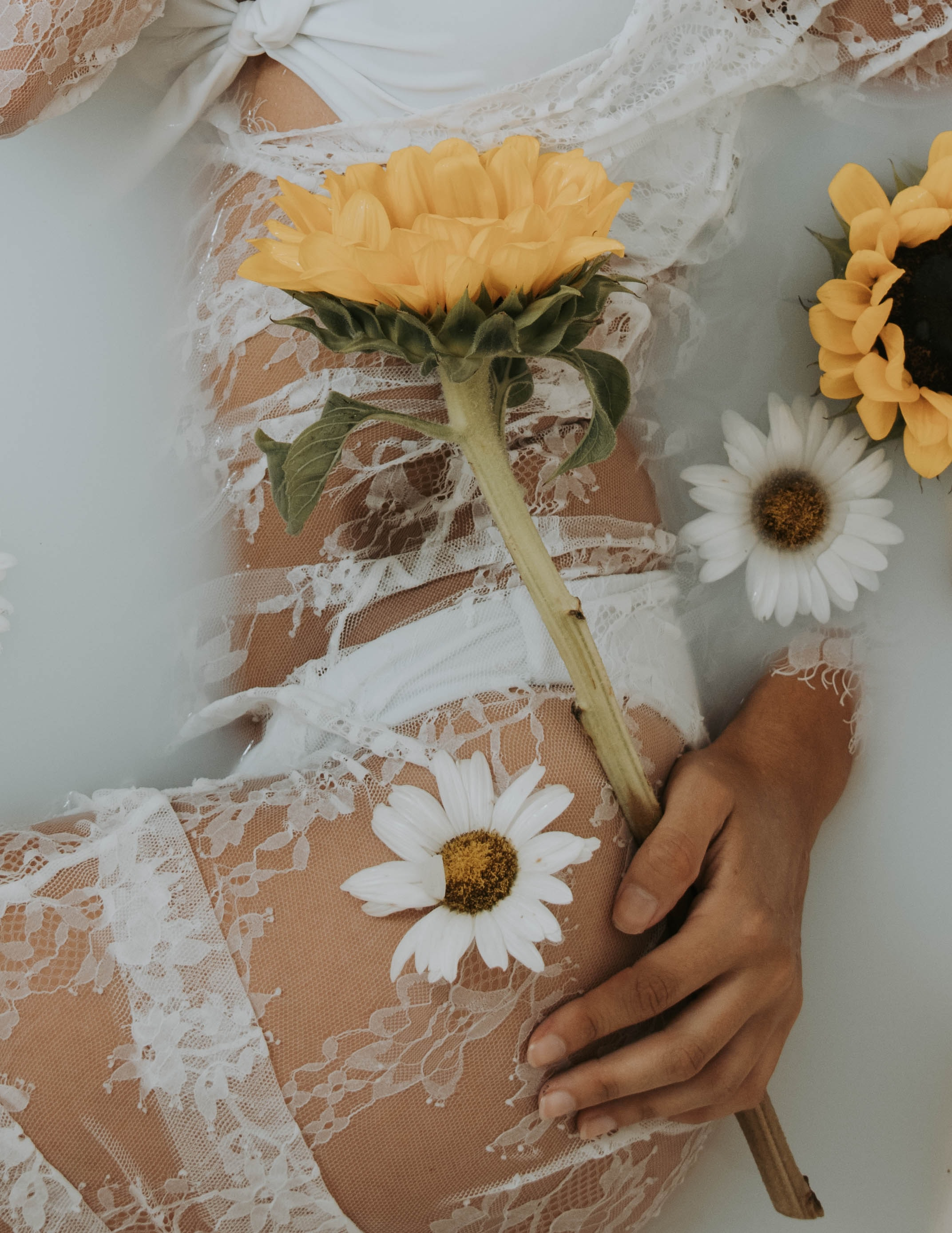 woman in white lace lingerie holding sunflower