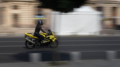 shallow focus photo of man riding on yellow sport bike during daytime honda zoom background