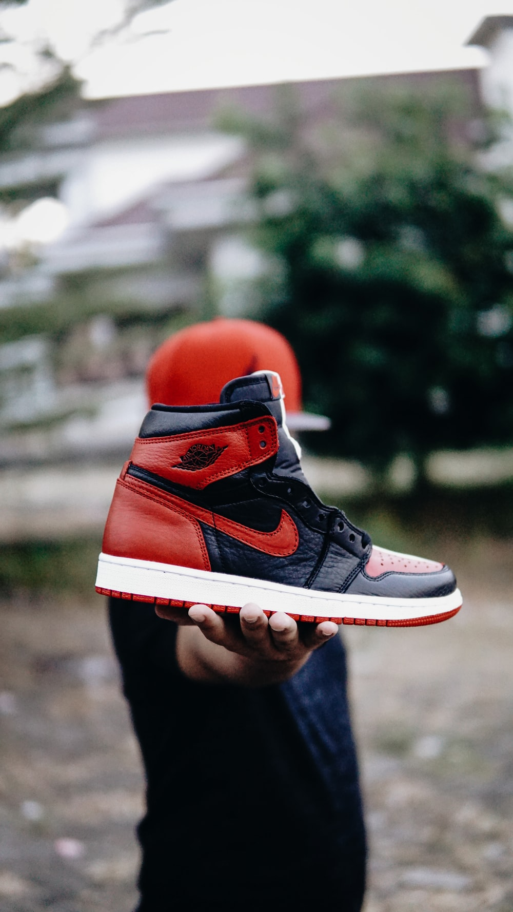 selective focus photo of person holding unpaired black and red Nike Air  Jordan 1 shoe 87f25090f