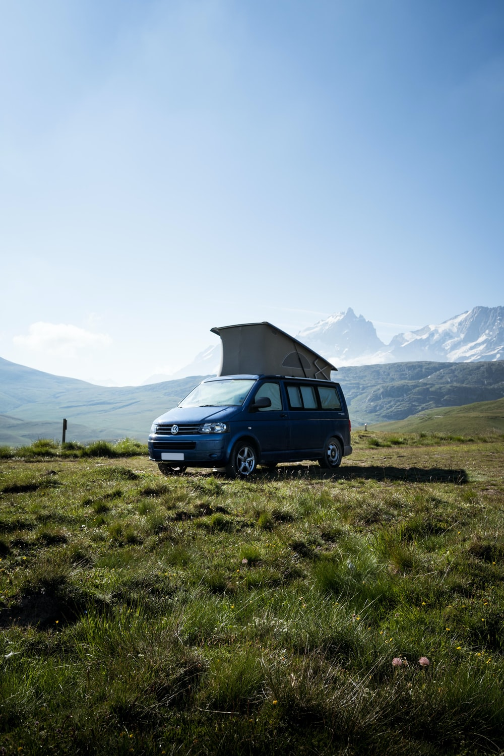 blue Volkswagen Transporter van on green grass field