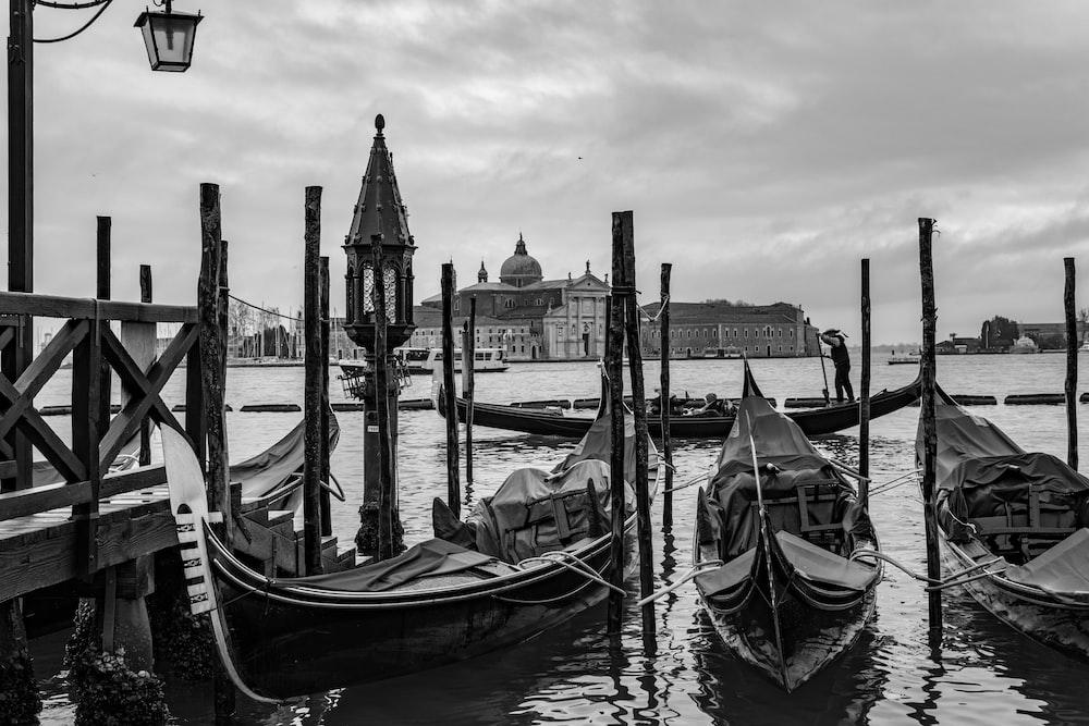 grayscale photo of boats near dock