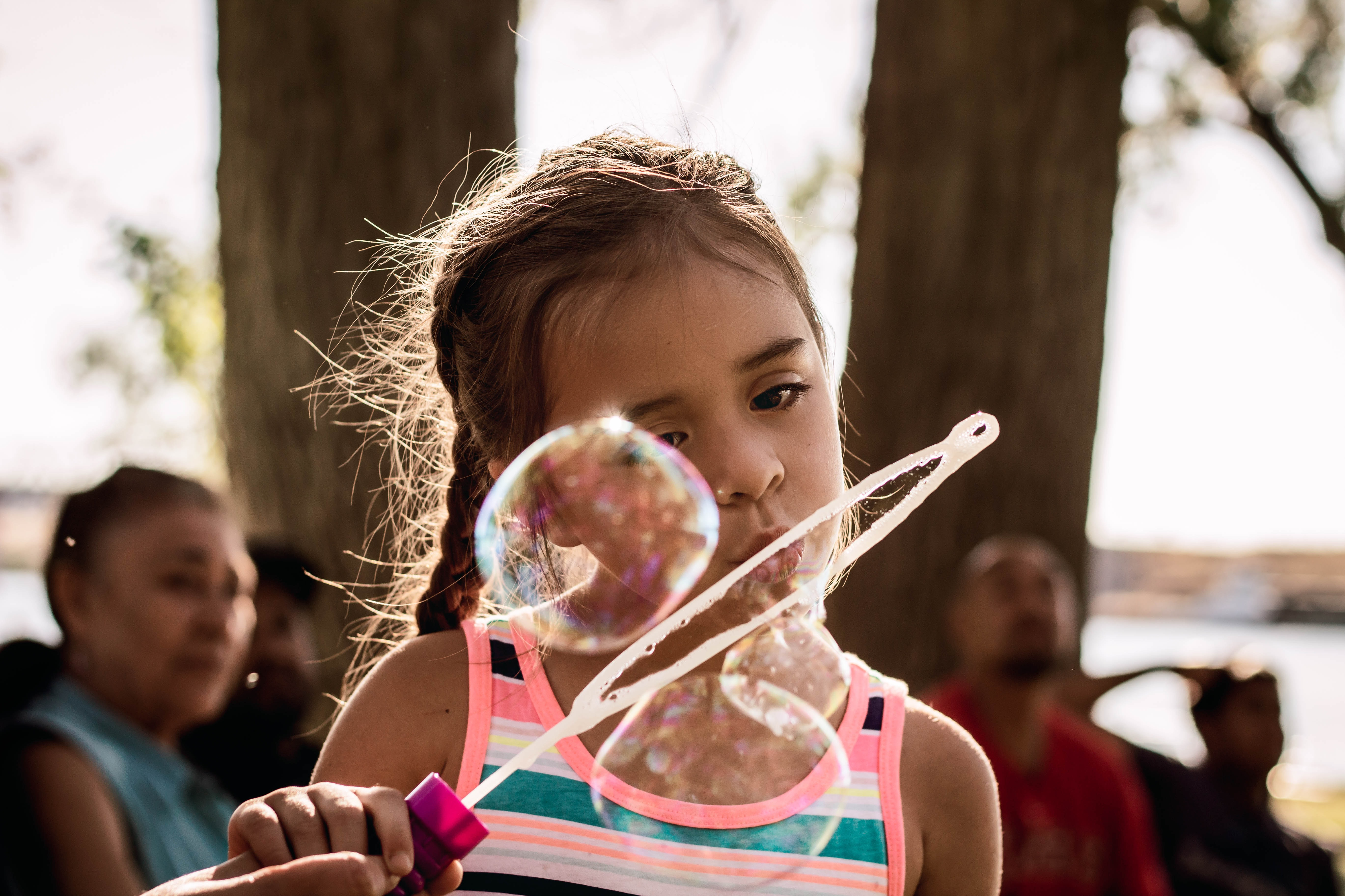 girl blowing bubble during daytime