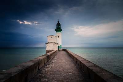 white and green lighthouse beside sea