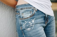 person in blue denim bottoms leaning on white surface