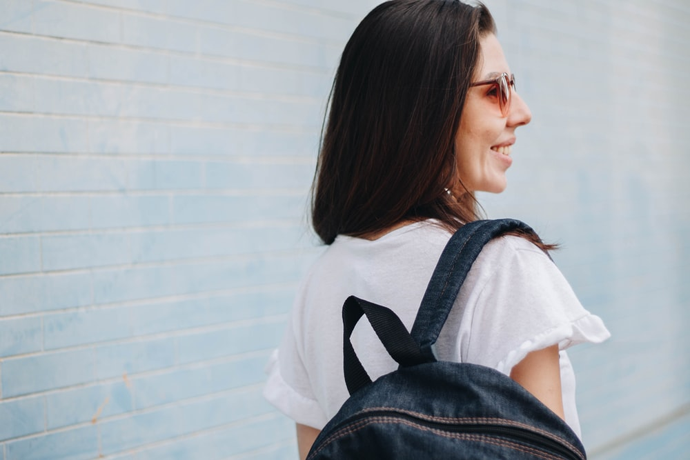 woman smiling while carrying blue denim backpack