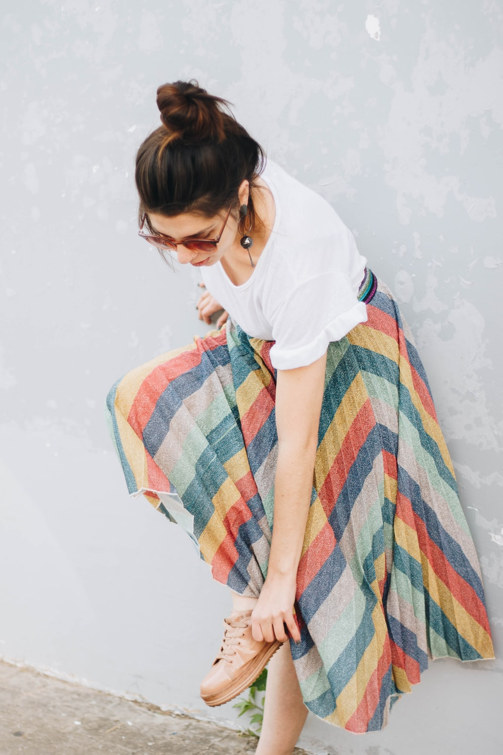 woman wearing white shirt and yellow, blue, and green striped long skirt