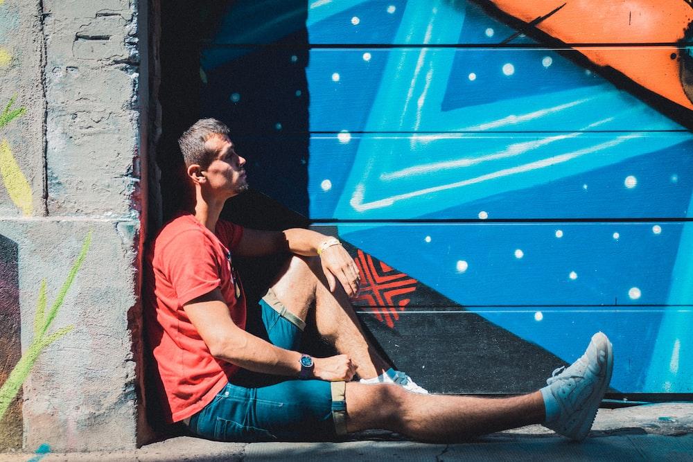 man sitting on floor leaning wall near graffiti wall during daytime