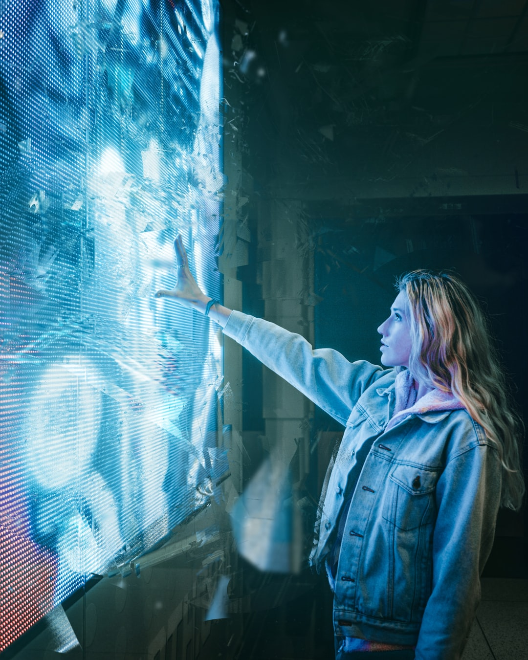 An image of a woman standing before a wall-sized blue display, reaching out as if controlling it with her hand.
