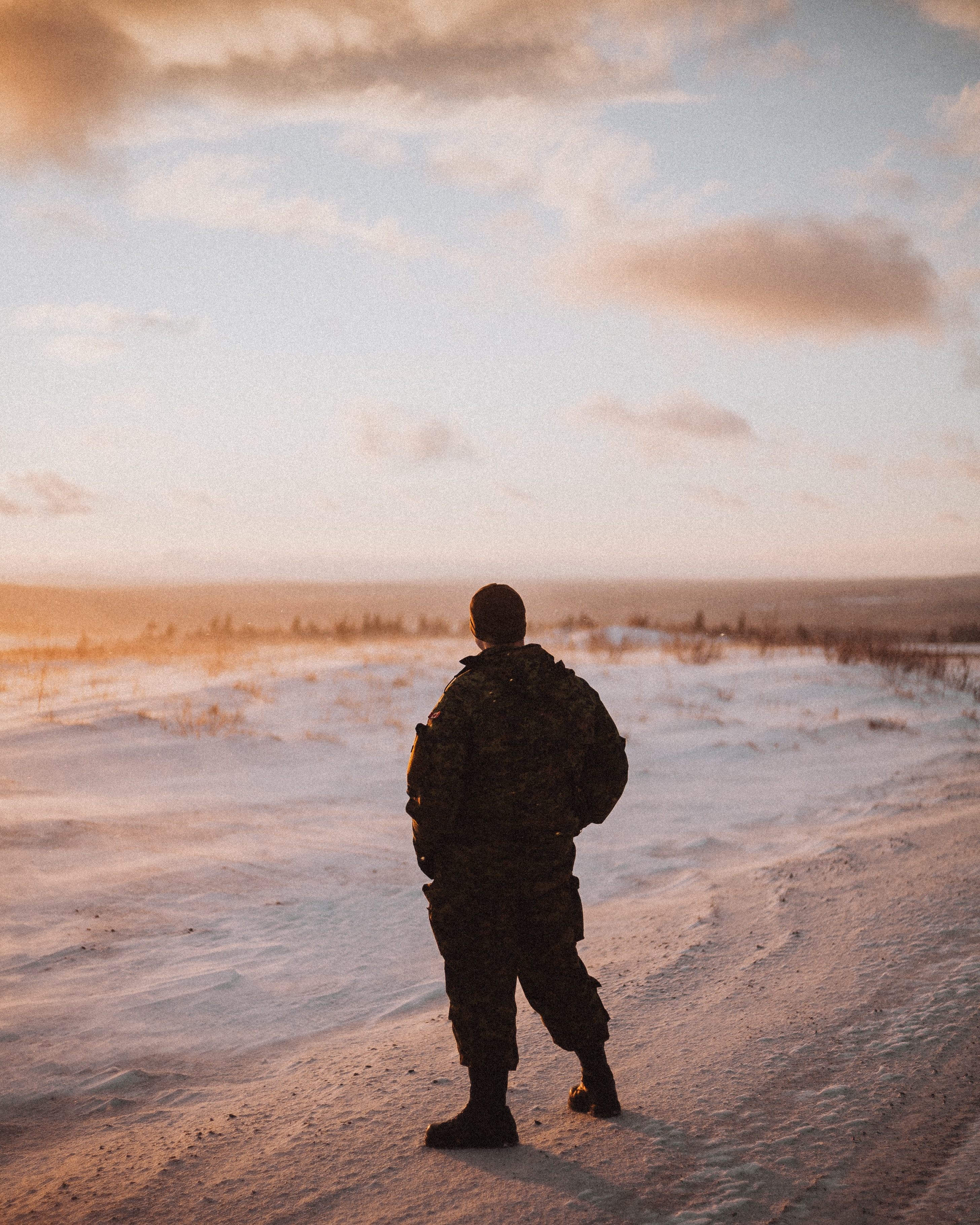male soldier standing on sand dunes