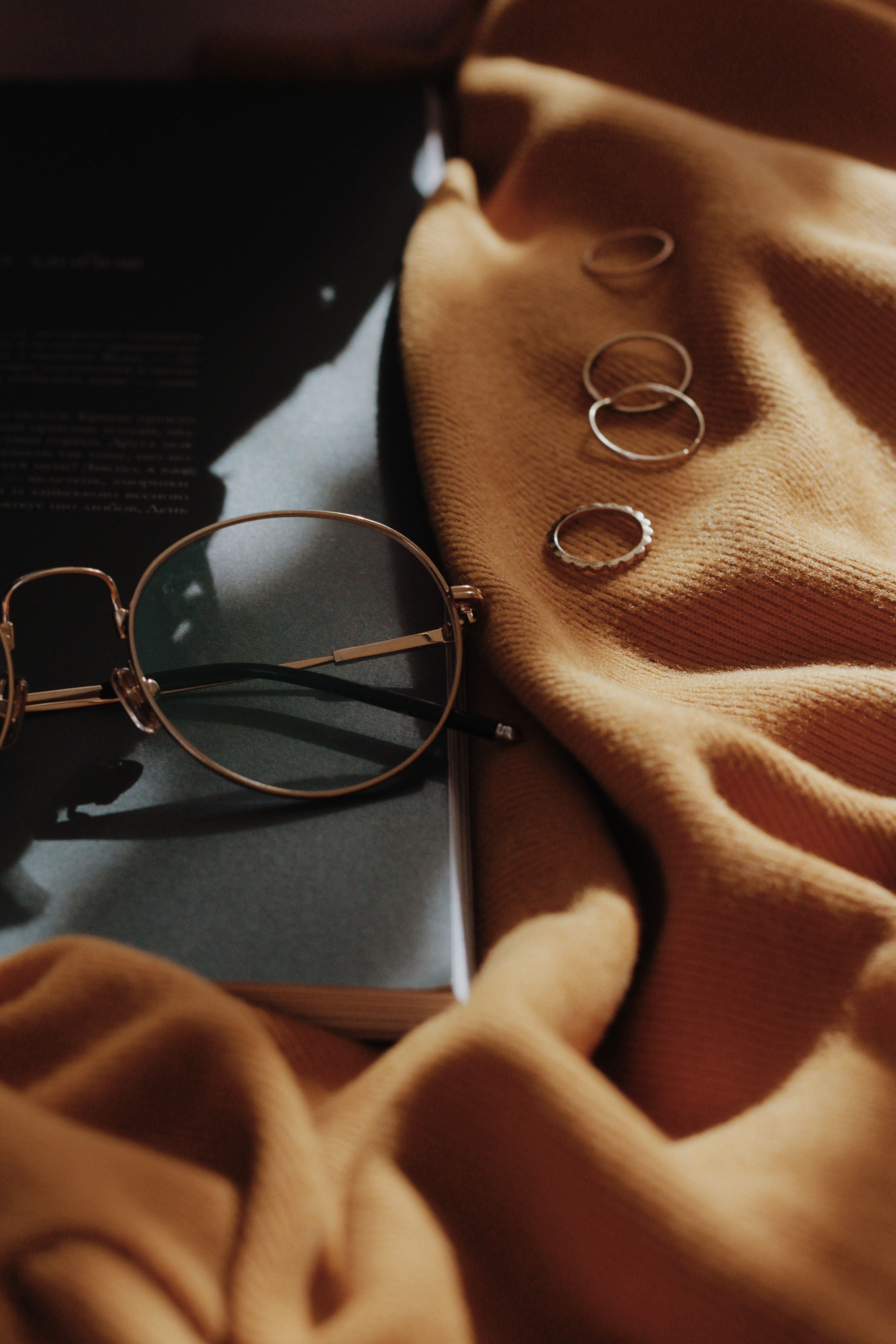 gray framed eyeglasses near four copper-colored accessories on orange sheet