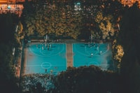 basketball court surrounded by green leafed trees