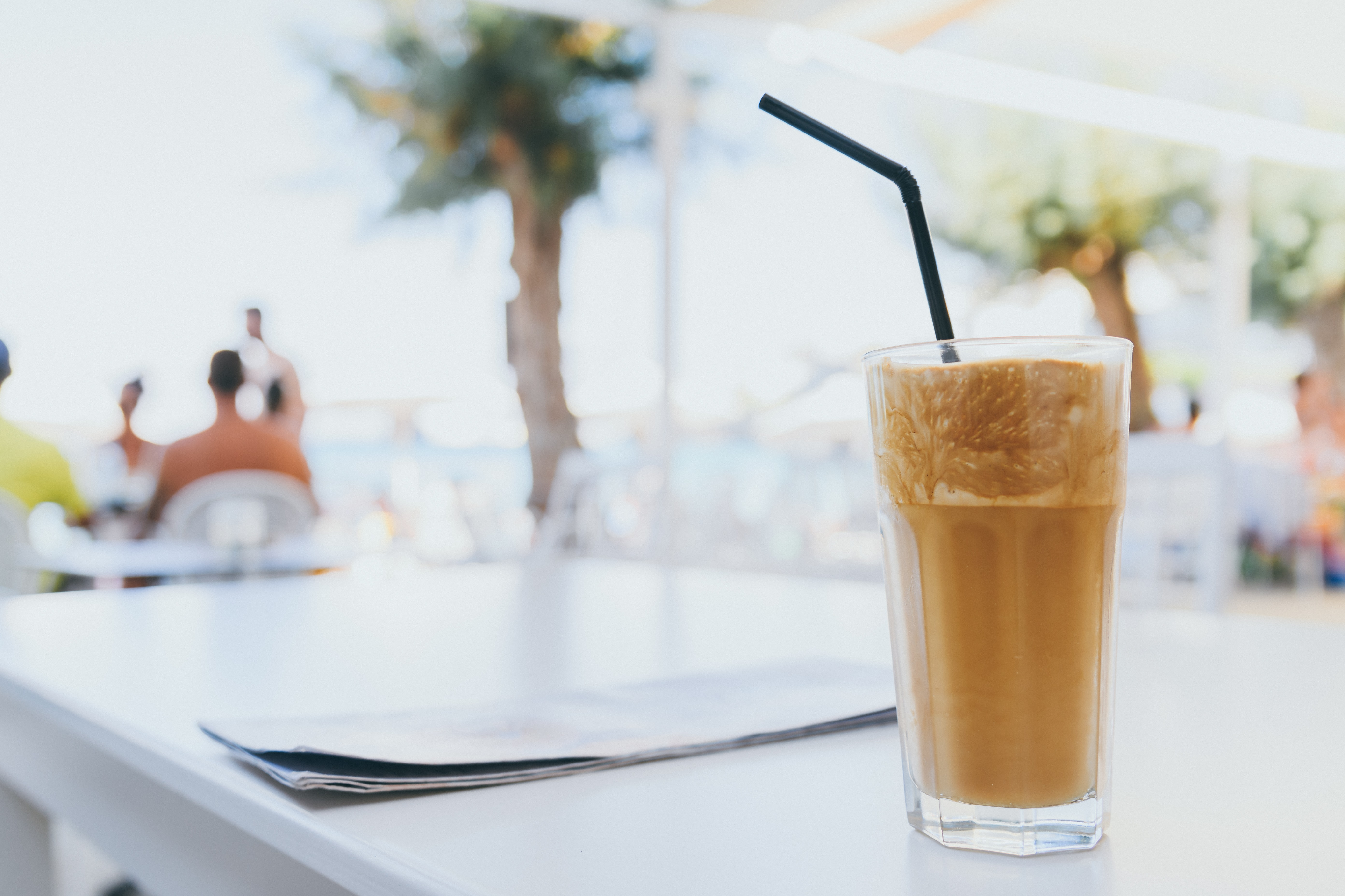 filled drinking glass with black straw