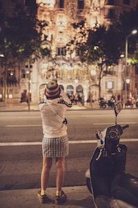 woman standing beside gray motor scooter near building