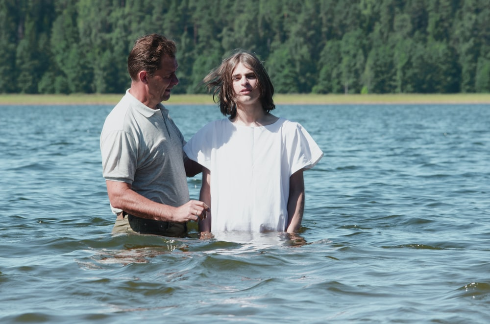 two man standing on body of water near trees at daytime