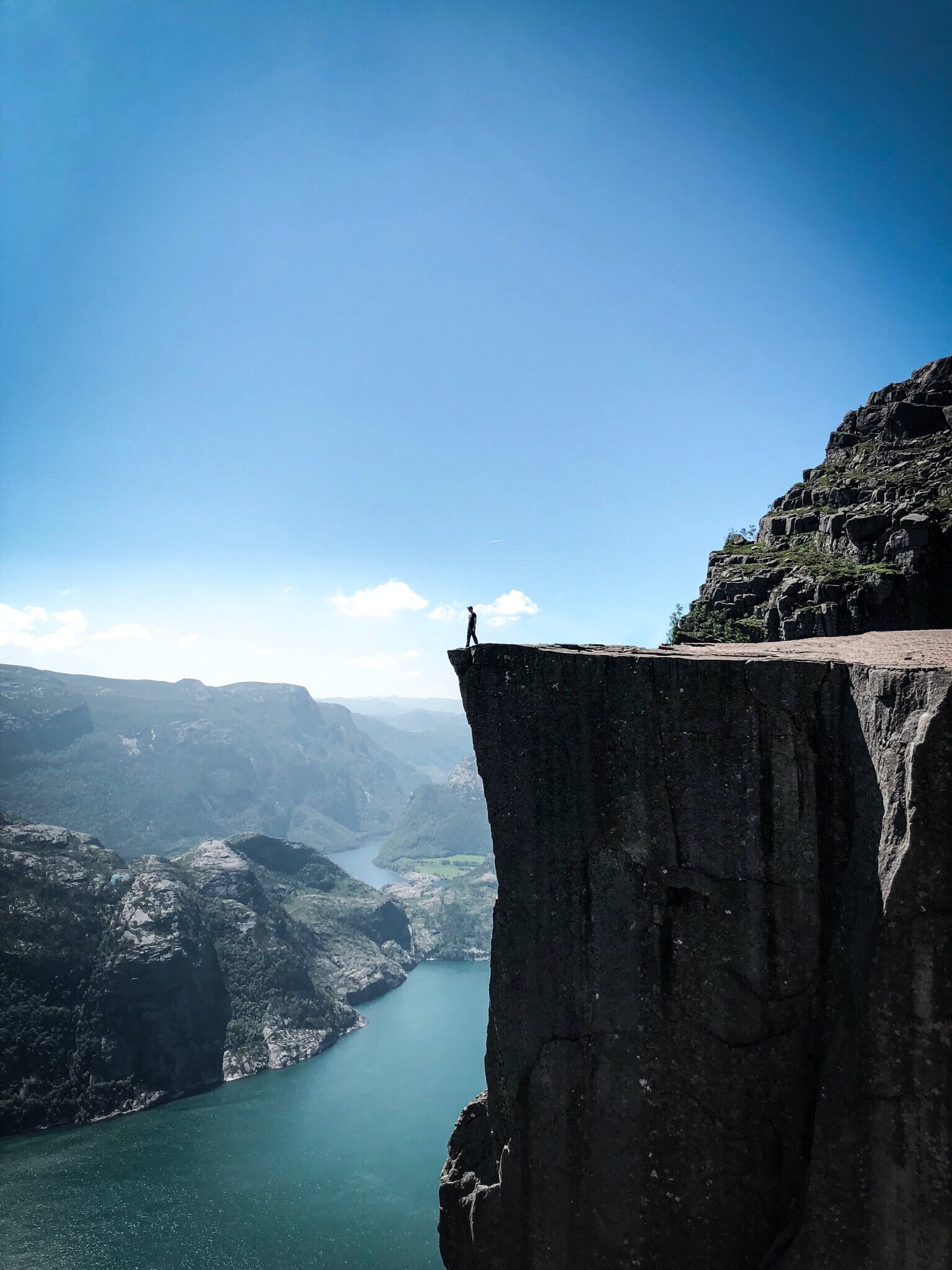 man standing on the edge of the rocky cliff looking down