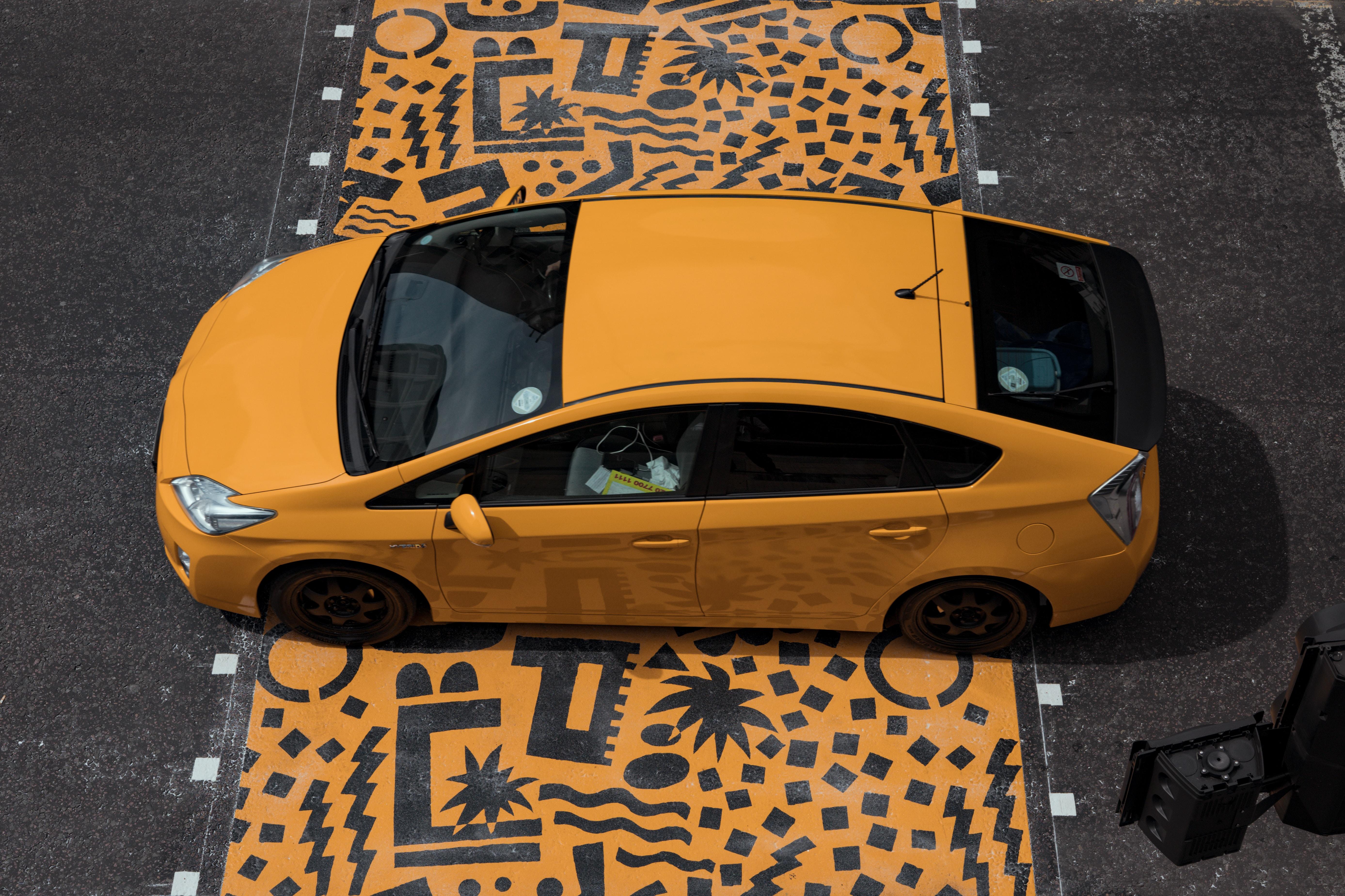 yellow sedan parked on yellow and black floor