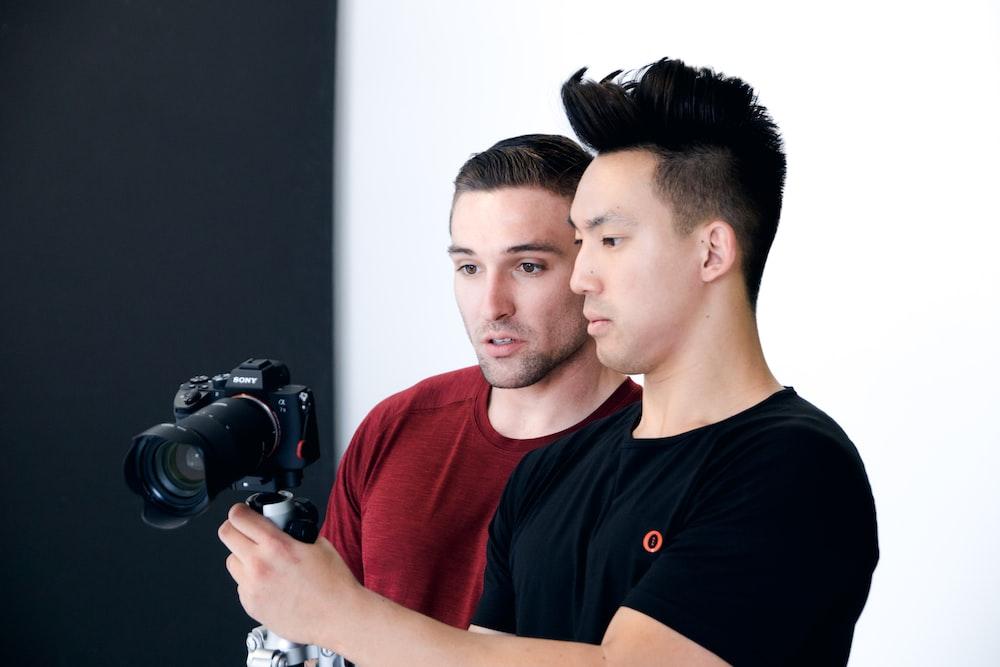 man holding black DSLR camera