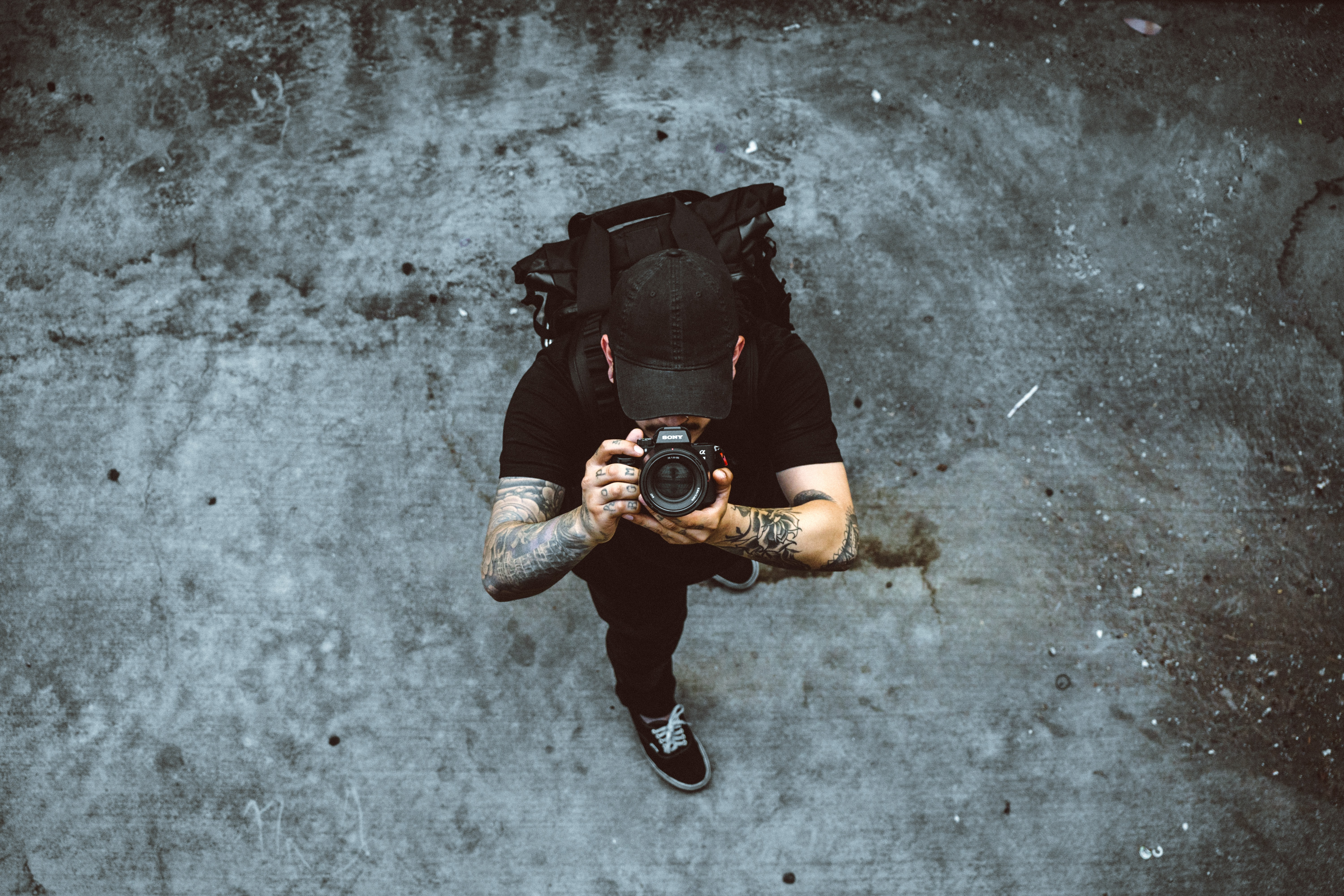 man taking photo while standing on gray concrete ground