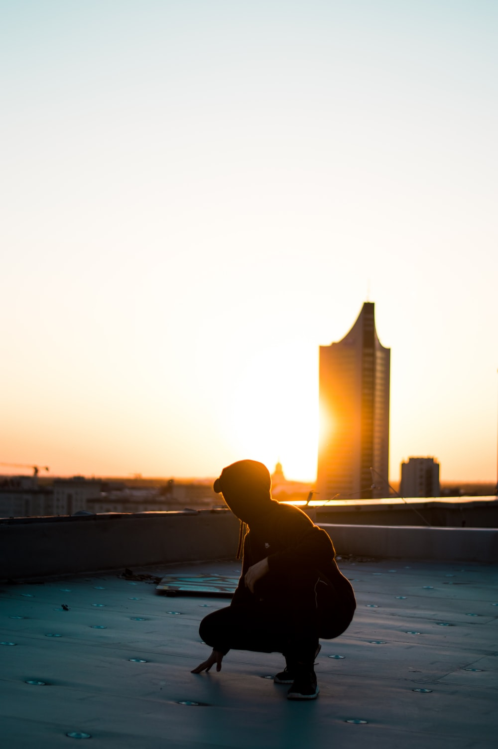 silhouette photography of woman squatting on rooftop