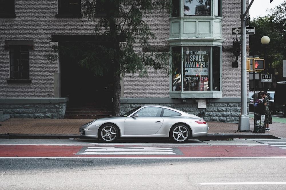 silver Porsche coupe parked near building