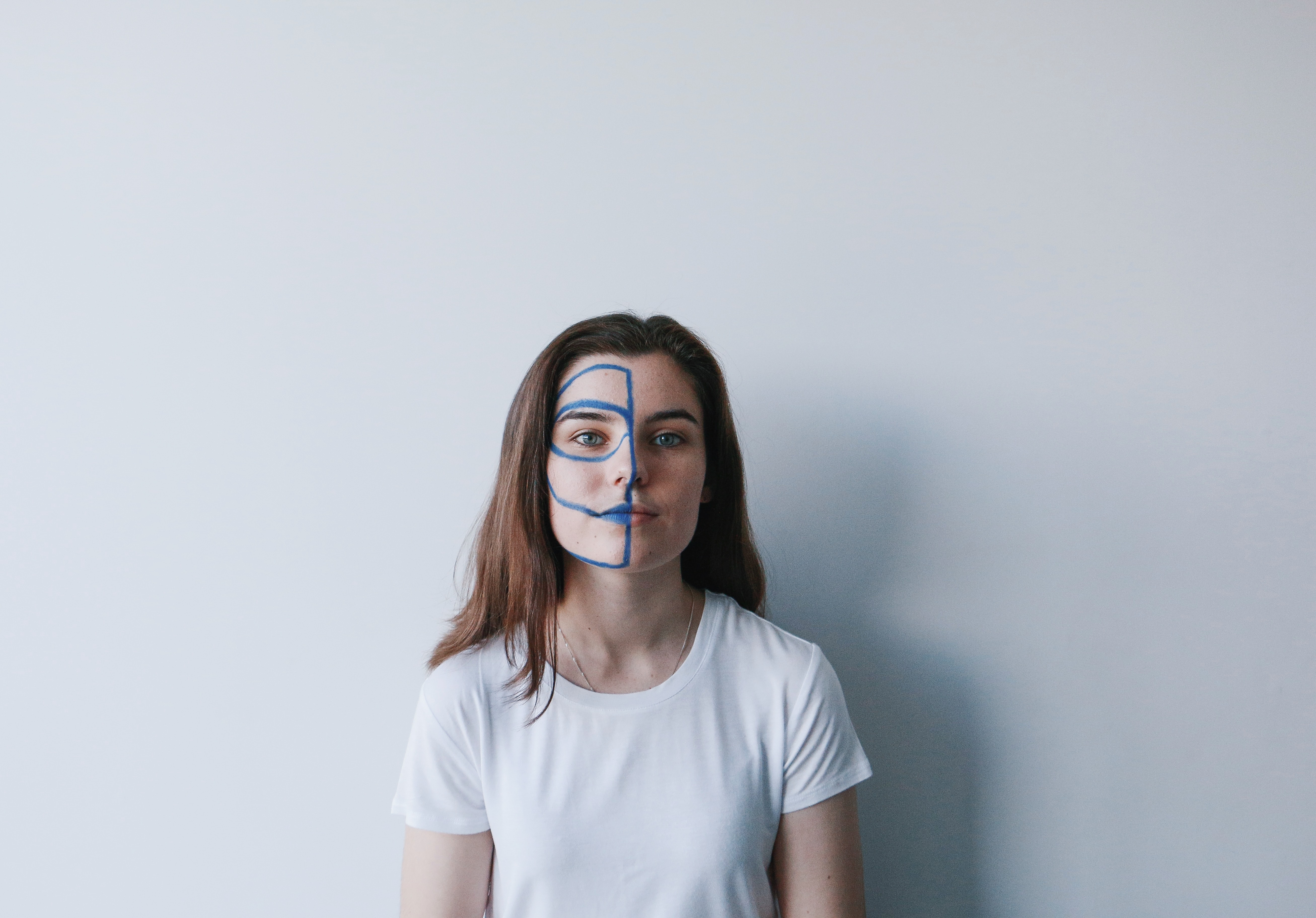 woman wearing white crew-neck t-shirt with mask on face leaning on wall