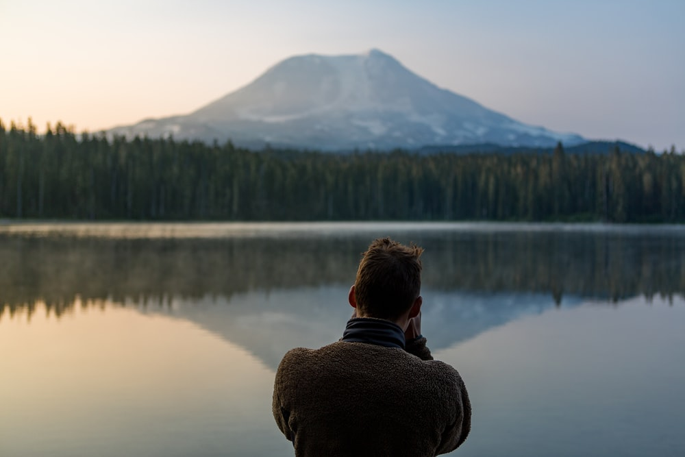 photo of person standing in front of water and forest