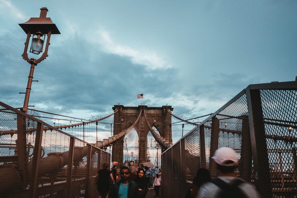 photo of people walking on Brooklyn Bridge