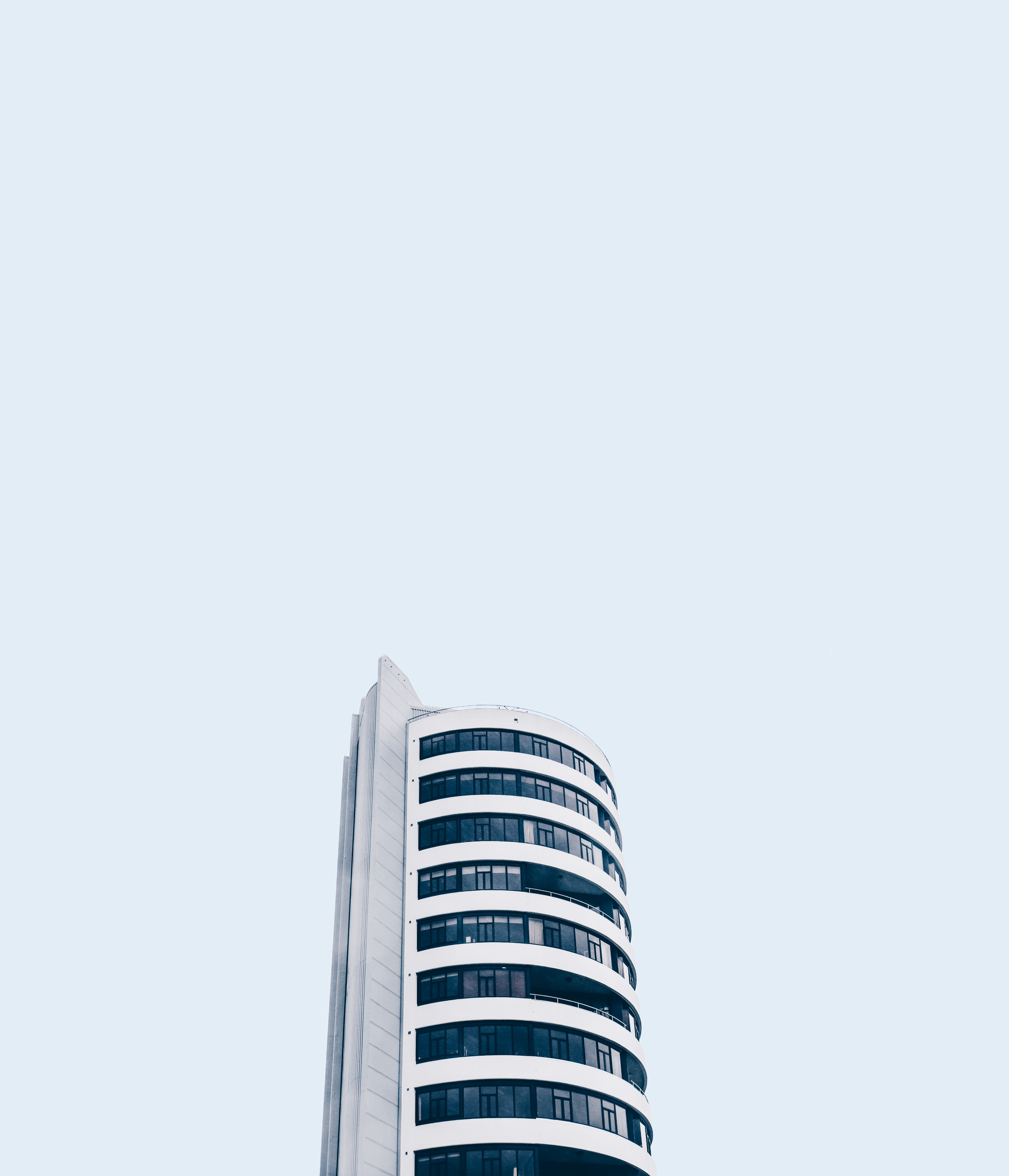 low angle photo of white high rise building under white sky at daytime