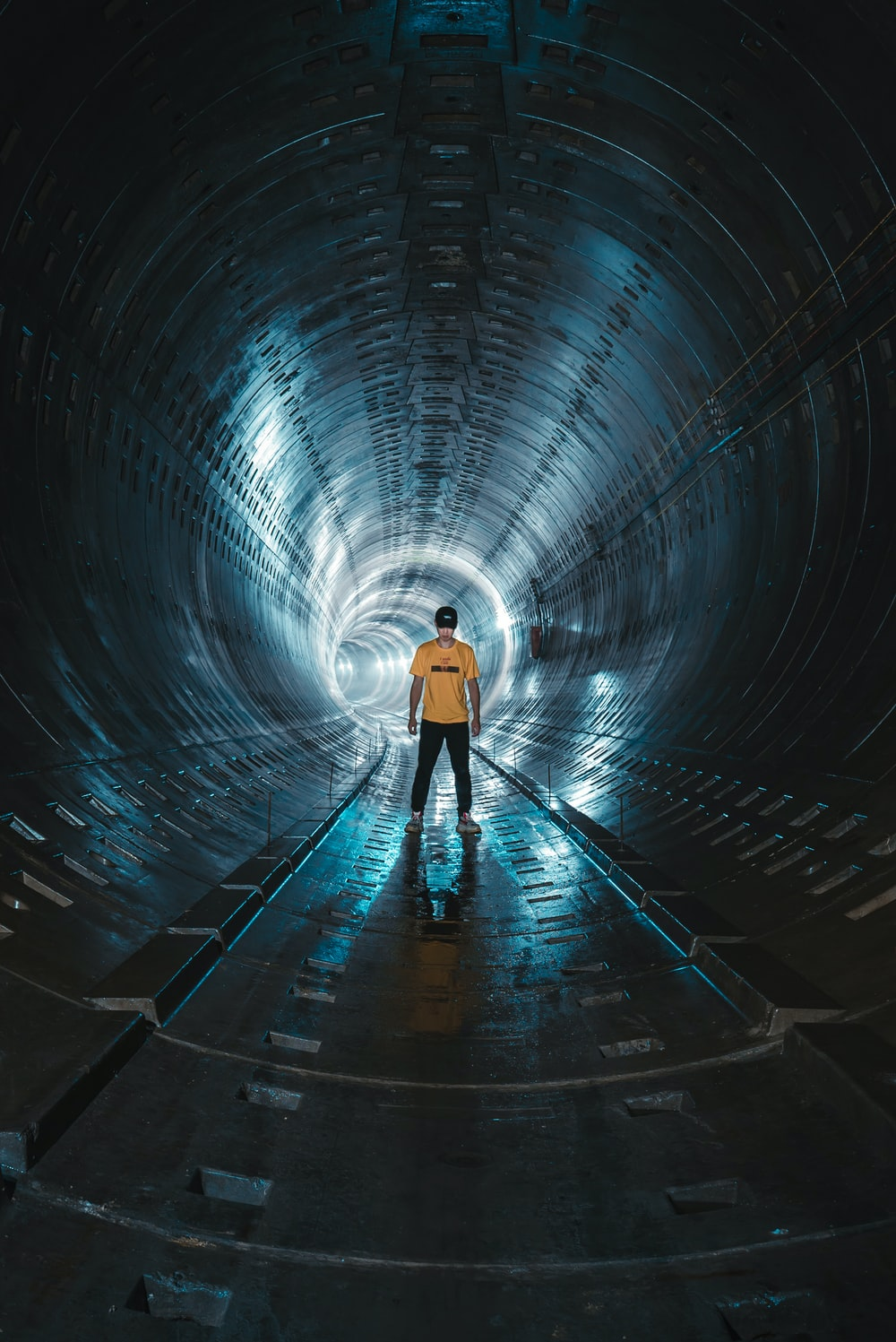 low light photography of man standing inside tunnel