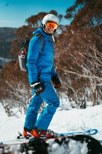 man in blue snow suit riding snowboards