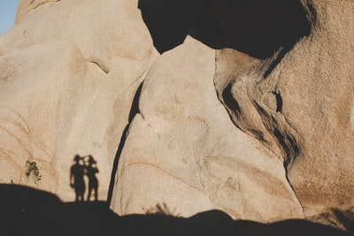 photo of human shadow on brown mountain during daytime