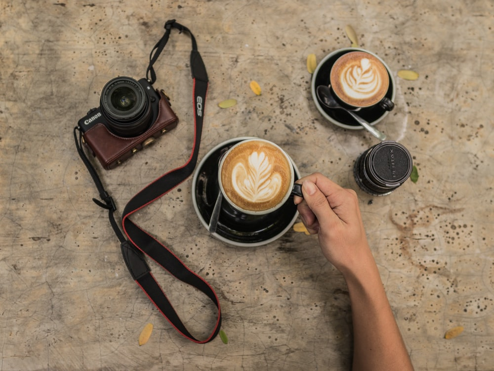 person holding black ceramic mug filled with latte on round black and white ceramic saucer near black and brown Canon DSLR camera