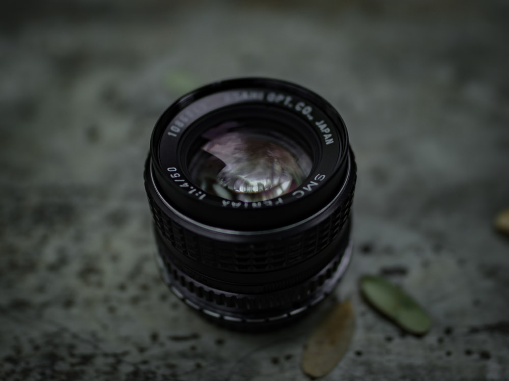 selective focus photography of black camera lens on brown surface