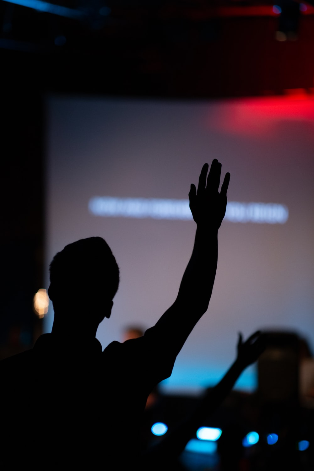 silhouette of person raising hand