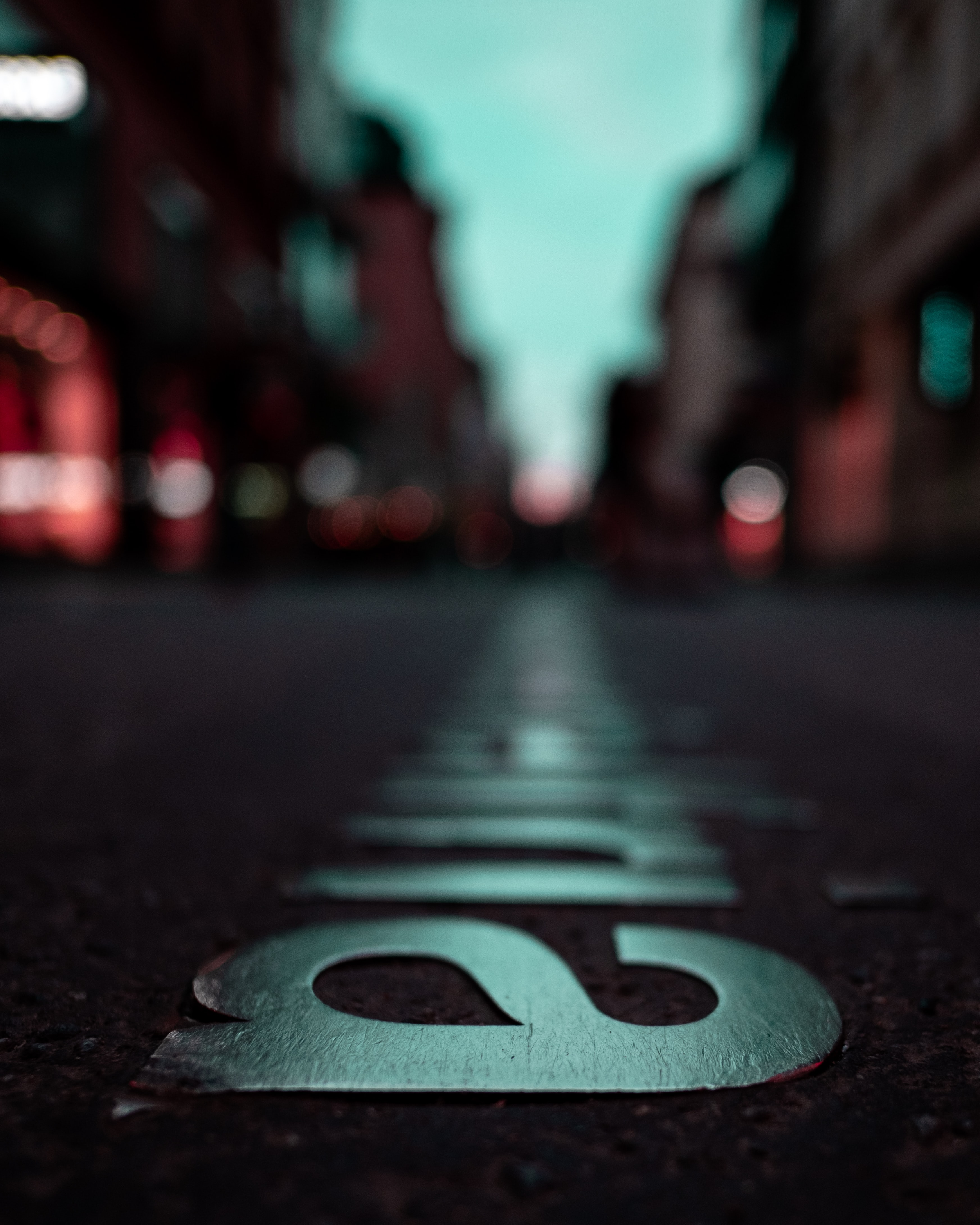selective focus photography of silver-colored emblem on concrete pavement