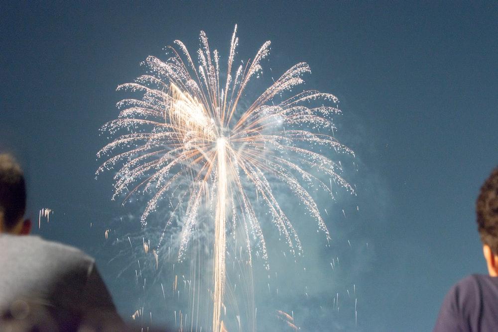 people watching fireworks display at nighttime