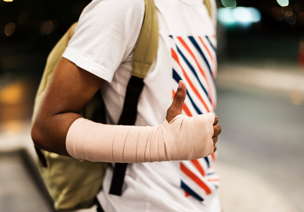 man with hand bandage wearing backpack standing