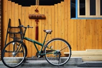 green bike beside wooden wall