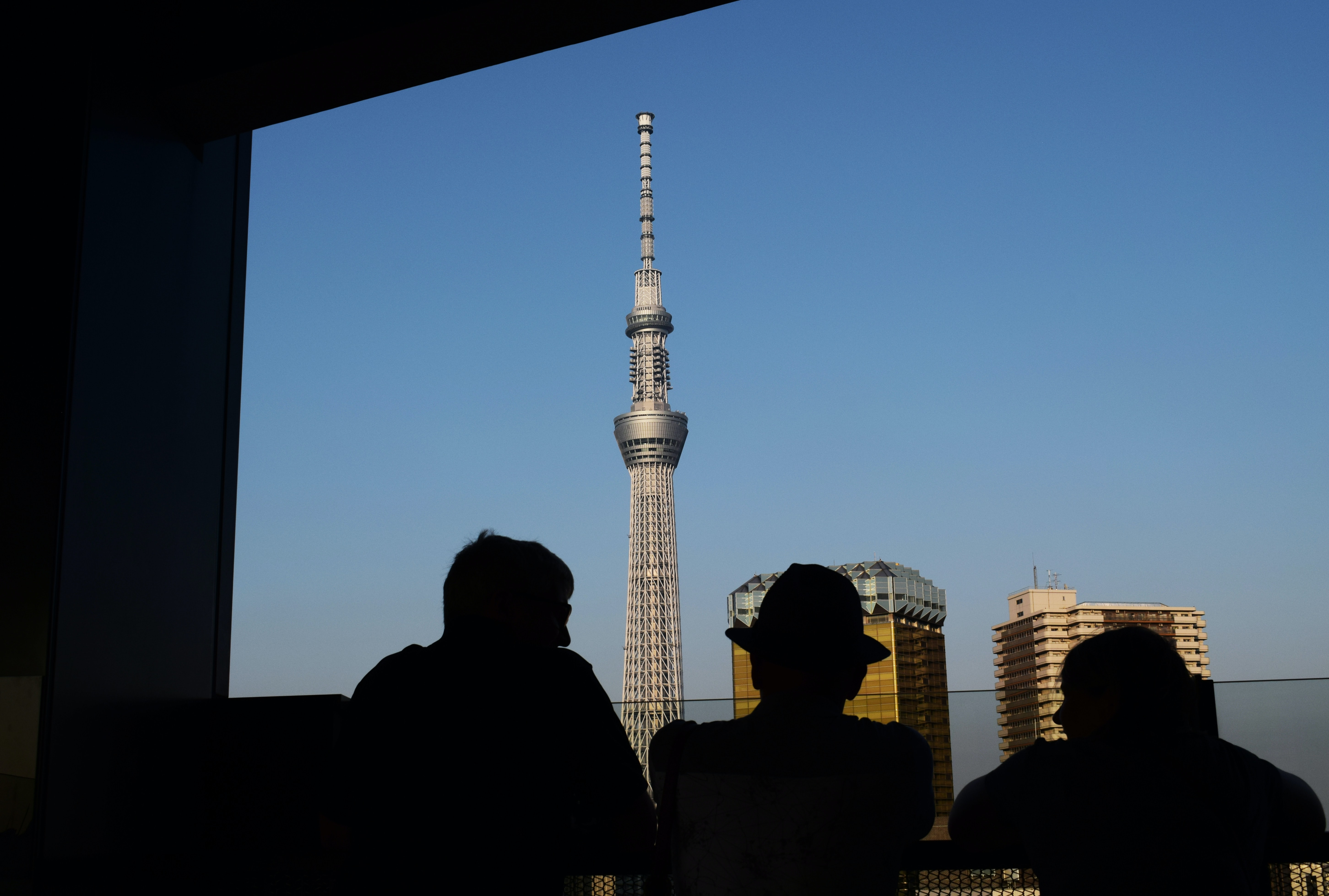 three silhouette of persons standing in front window watching tower building