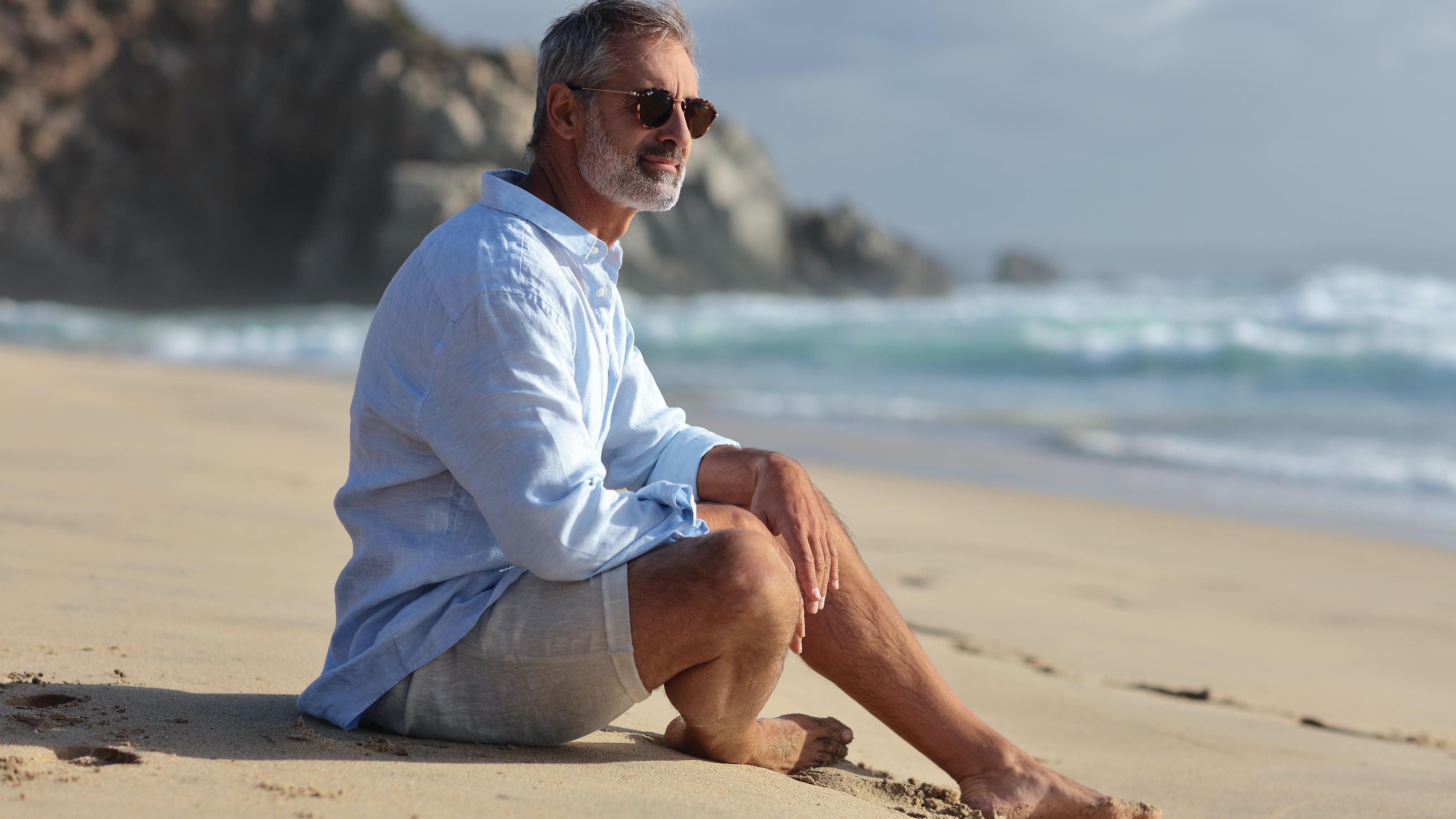 man wearing blue dress shirt sitting on seashore at daytime