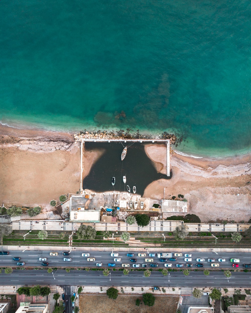 aerial photography of seashore near buildings and concrete road top during daytime