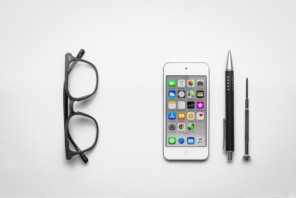 white iPod touch beside click pen