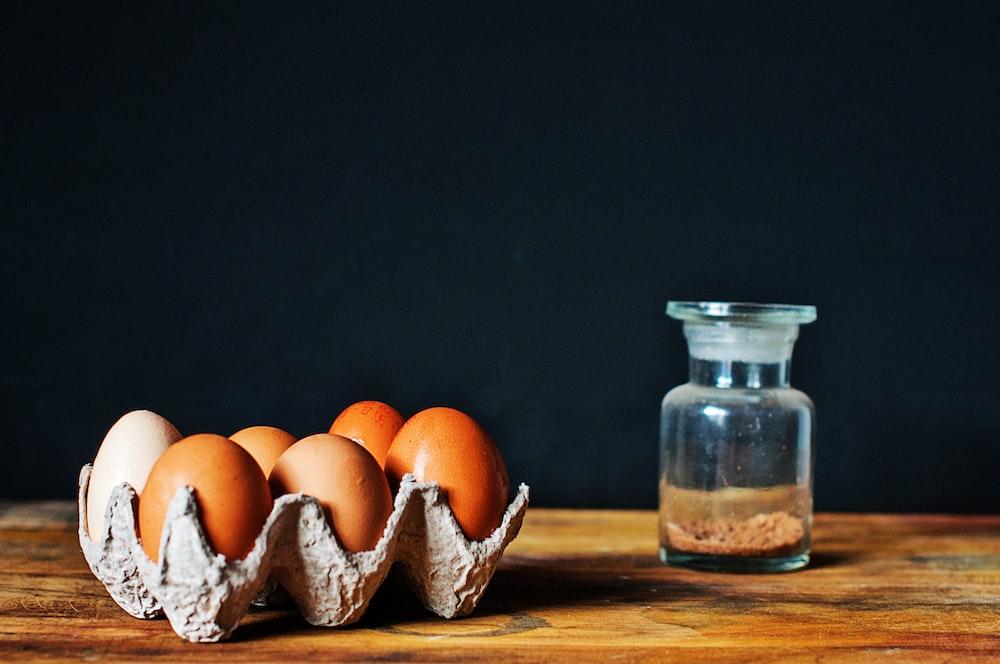 brown eggs in tray near clear glass bottle
