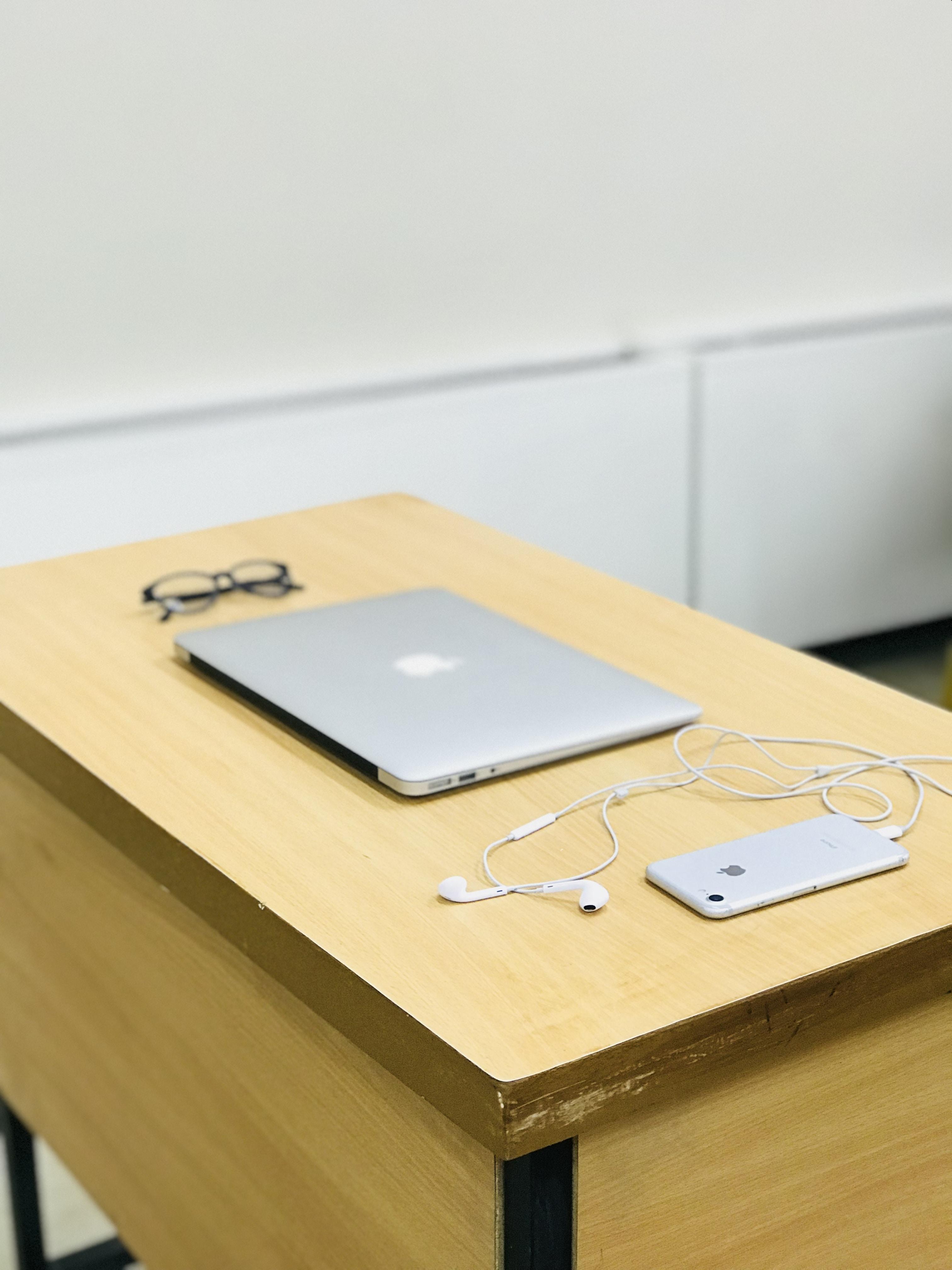 silver MacBook beside eyeglasses and iPhone