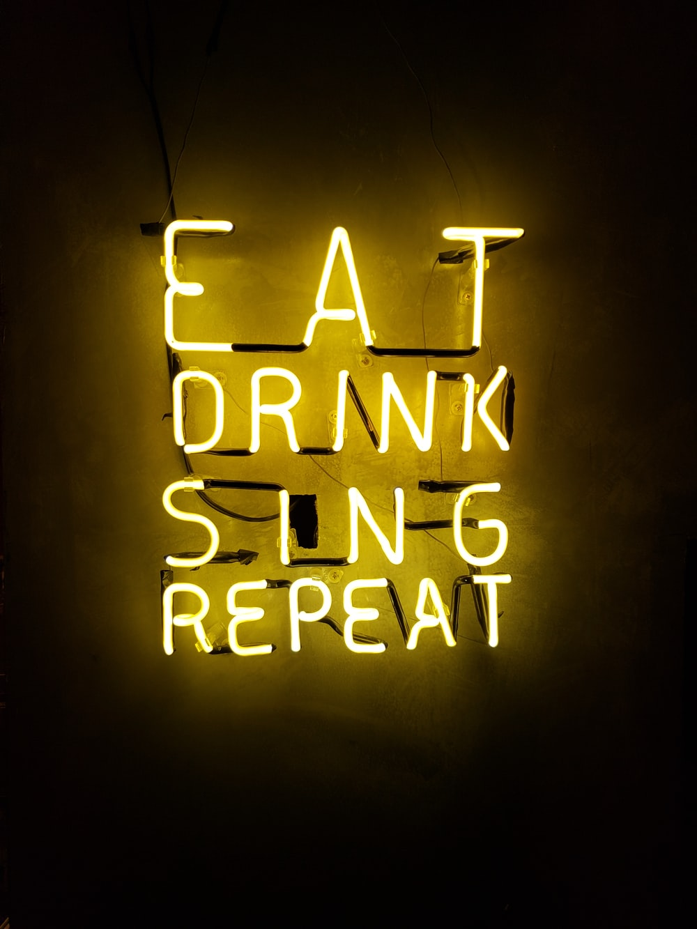 turned on eat drink sing repeat neon signage on wall