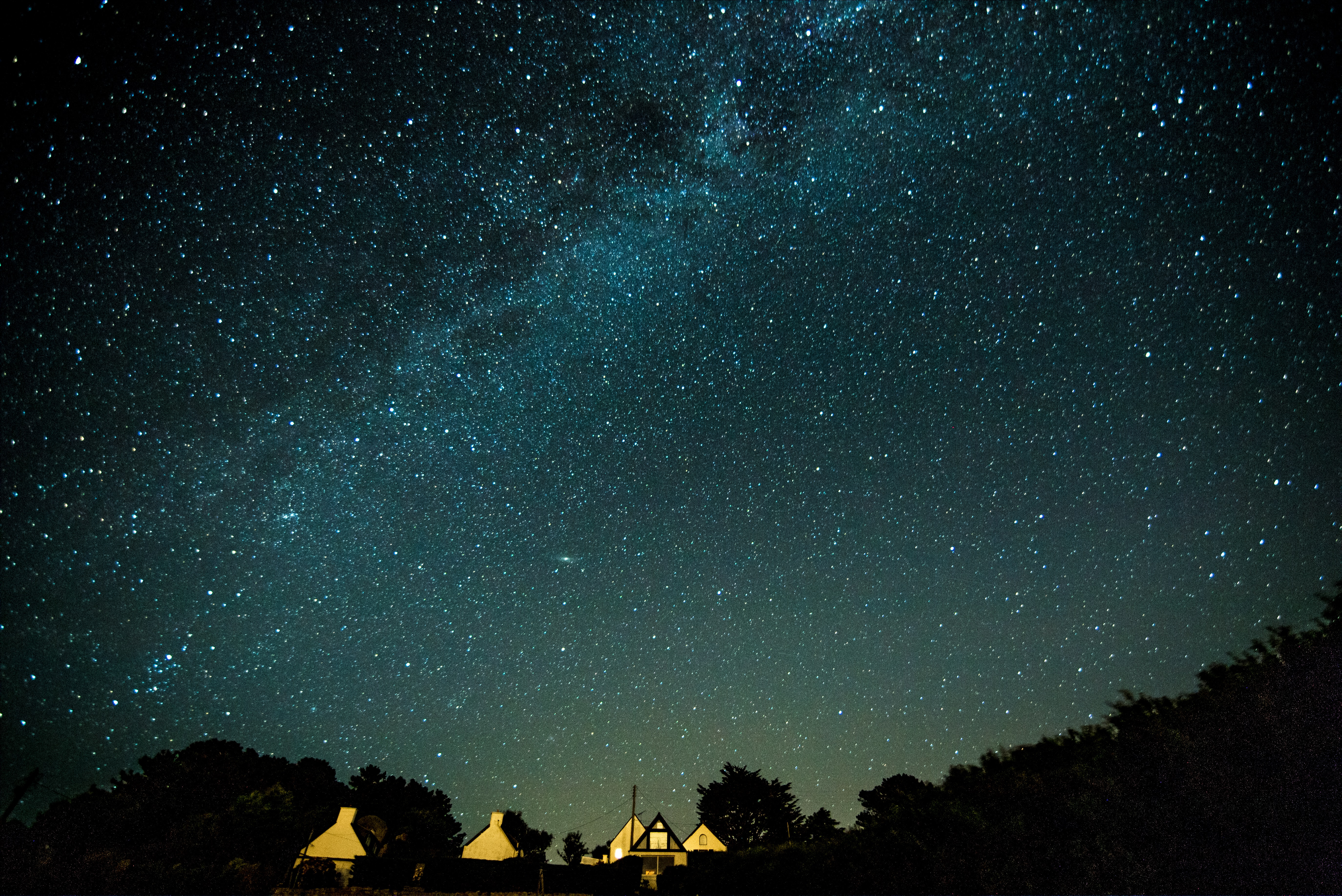 lighted house under sky with stars at night