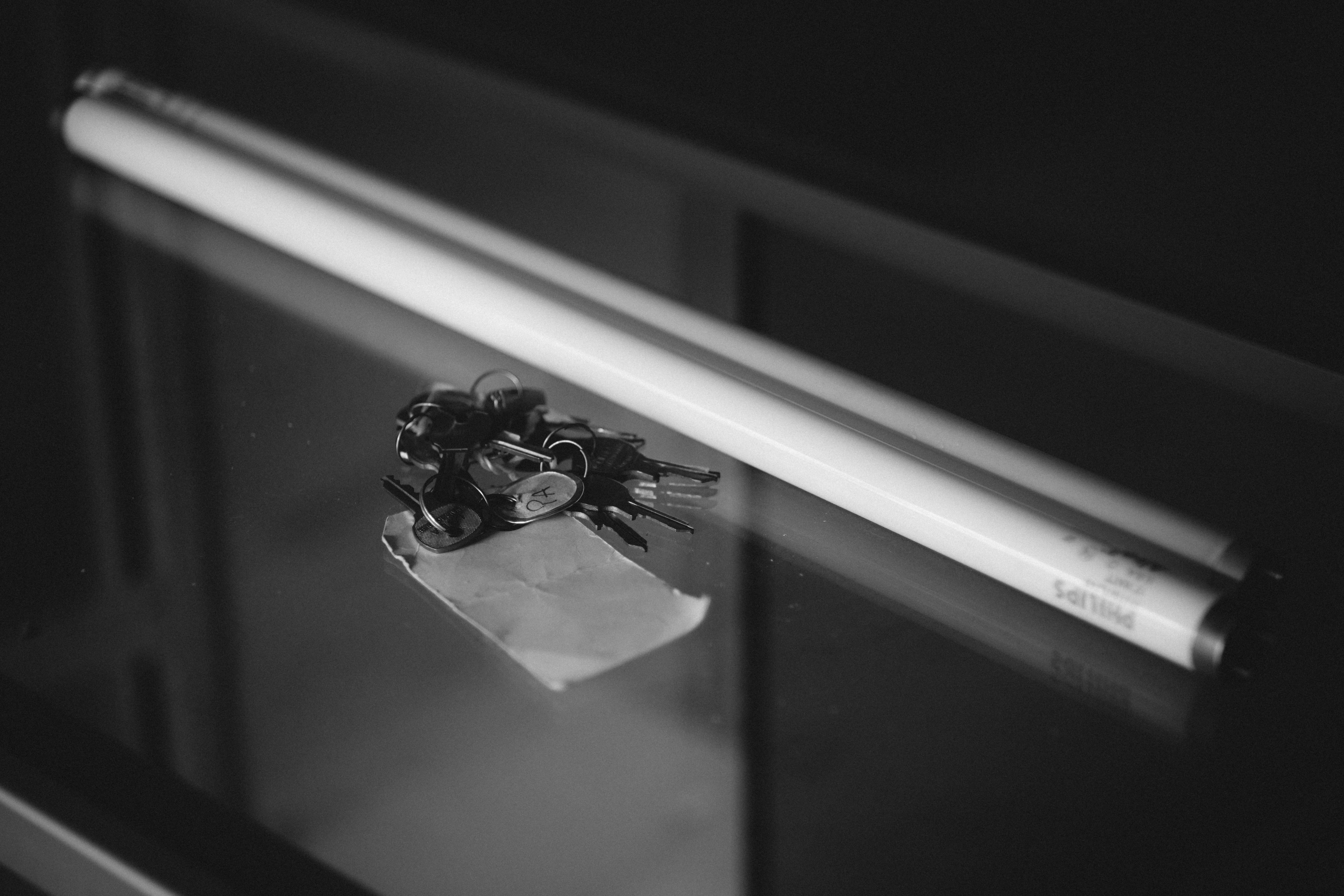 grayscale photography of fluorescent light tube placed beside keys