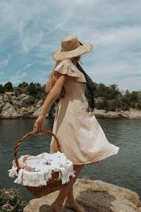 woman carrying brown wicker basket
