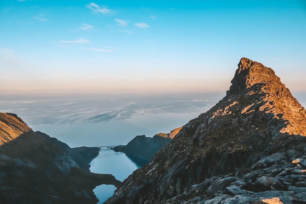 gray mountain peak near body of water